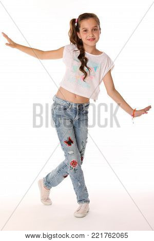 Pretty beautiful happy brunette young teen girl in blue jeans and a bare belly. The adorable slender smiling preteen standing in sports shoes. The image of children's summer fashion. poster