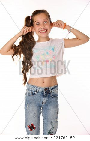 Portrait of beautiful cheerful brunette young teen girl  smiley face ape. The child playing tricks. Laughing preteen in blue jeans and a bare belly is an image of children's summer fashion. poster