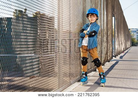 Portrait of preteen boy, happy roller skater in helmet and protective gear, standing alone at outdoor rollerdrom