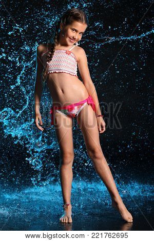 Happy young teenage girl in a swimsuit stands barefoot in splashing water. Pretty child with dark hair and beautiful face adorably smiles. Slender preteen in a bikini. poster