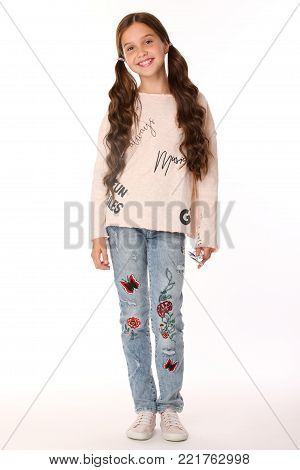 Pretty beautiful happy brunette young teen girl in blue jeans. The adorable slender smiling preteen standing in sports shoes. The image of children's summer fashion. poster