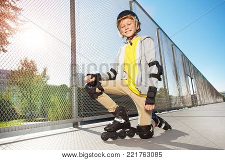 Portrait of smiling preteen boy, roller skater in protective gear, posing on floor at skate park
