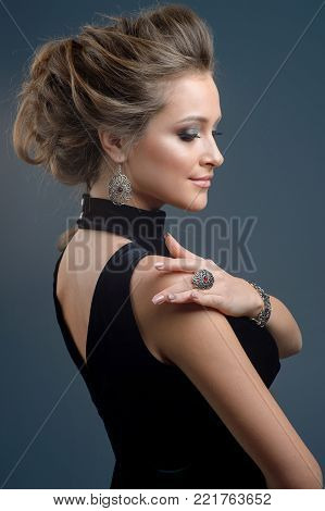 Beauty and Jewelry woman in black dress modern style with hairstyle and silver  jewelry. Fashion brunet model with necklace earrings in fashionable jewelry