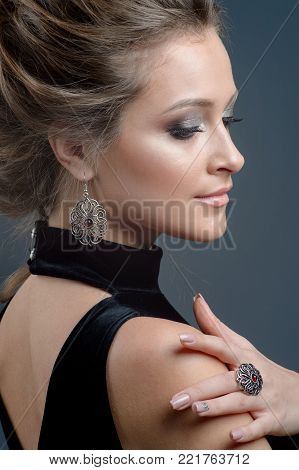 close-up portrait beautiful young woman wearing luxury jewelry. Focus on earring