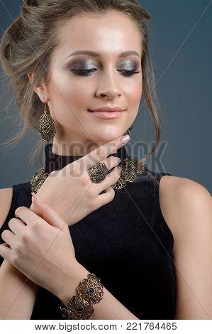 Beauty portrait of a brunette in jewelry on a dark blue background.