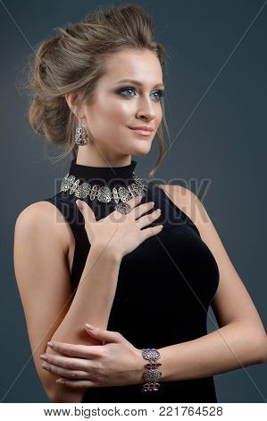 Fashion portrait of beautiful young woman in stylish. Beads around the neck of a woman. Stylish hairstyle and light makeup. Wearing bracelet necklace earring and finger ring.