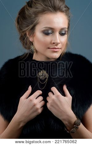 Fashion woman portrait. Elegant lady with hairstyle,  jewelry brooch and earrings  posing isolated on studio dark blue background.