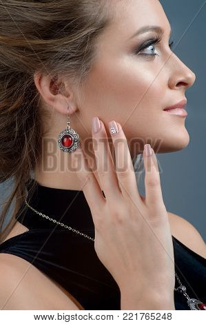 Pretty woman model wearing luxury silver accessory and jewelry. Girl Isolated on dark blue background