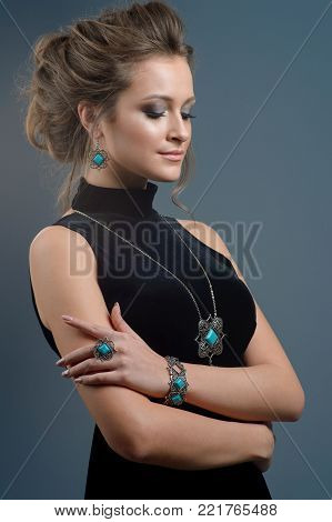 luxury jewelry and fashion concept. A model demonstrate jewelry collection - bracelet earrings necklace and ring on dark blue background