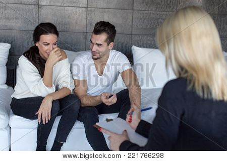 Couple smiling and joking on therapy at psychiatrist indoors