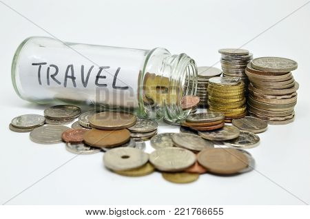 Travel lable in a glass jar with coins spilling out isolated on white background