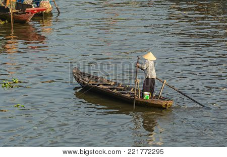 Mekong Delta, Vietnam - Feb 2, 2016. A woman rowing boat at Nga Nam floating market in Mekong Delta, Vietnam. Nga Nam is one of many famous floating markets in Vietnam.