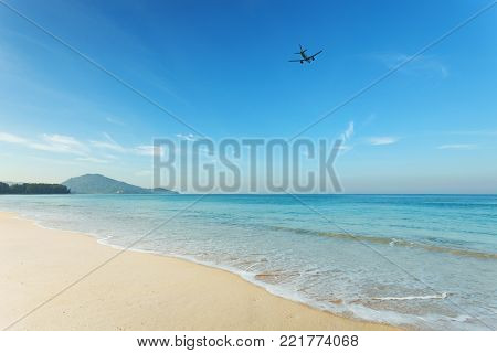 Tropical andaman seascape scenic off mai khao beach and wave crashing on sandy shore in phuket thailand with airplane takes off on sky,can be used for air transport to travel and open season to travel background