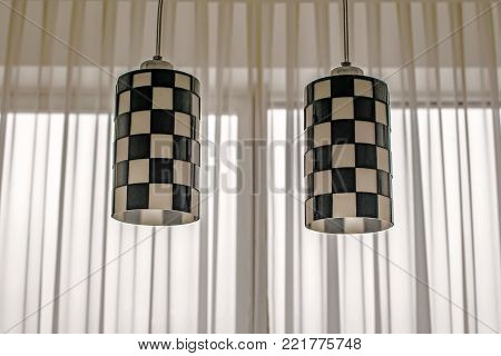Decor elements in an interior of modern room. Two ceiling lamps with Chess pattern plafonds, white transparent curtain, window. Minimalism. Black and White
