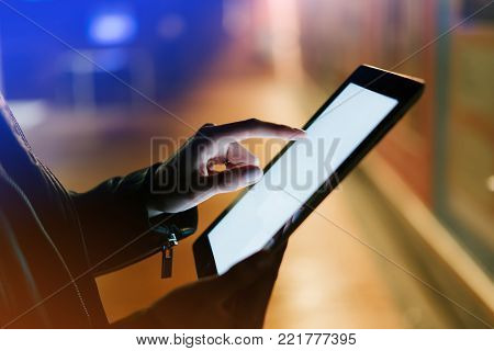 Girl holding in hands on blank clean screen tablet on background glow bokeh lights in night atmospheric city, hipster hands using template mobile computer on lights car glitter street; mockup gadget