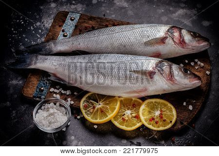 fresh raw sea bass fish with salt and lemon on wooden cutting board cooking concept on a dark background