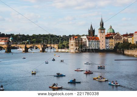 Panorama of Prague, a lot of catamaran floats on the river,  tilt shift effect