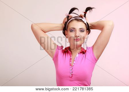 Portrait of childish young woman with pigtail. Infantile girl in headband doing fun on pink. Longing for childhood. Studio shot.