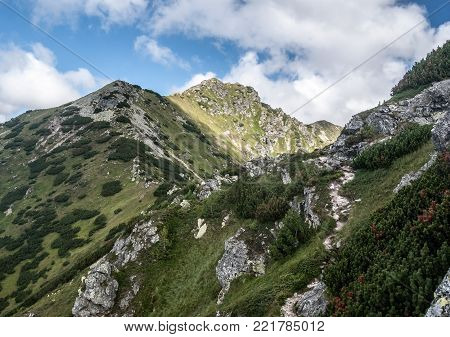partly rocky Otrhance mountain ridge with Nizna Magura, Ostredok and Vysna Magura peak in Western Tatras mountains in Slovakia during nice day with blue sky and few clouds