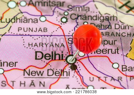 Close-up of a red pushpin on a map of Delhi, India.