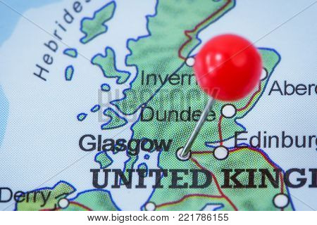 Close-up of a red pushpin in a map of Glasgow, United Kingdom.