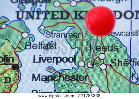 Close-up of a red pushpin in a map of Manchester, United Kingdom.