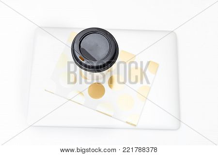 Paper cup with coffee and a laptop on a white background. Flat lay