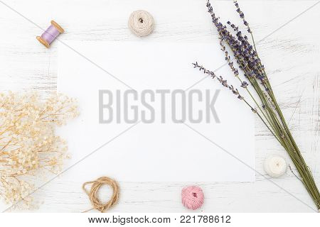 White blank card with flowers and ribbon on wooden background. Holiday concept