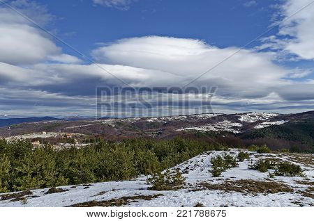 Majestic view of cloudy sky, winter mountain, snowy glade, residential district, conifer and deciduous forest   from Plana mountain toward Balkan mountain or Stara planina, Bulgaria, Europe