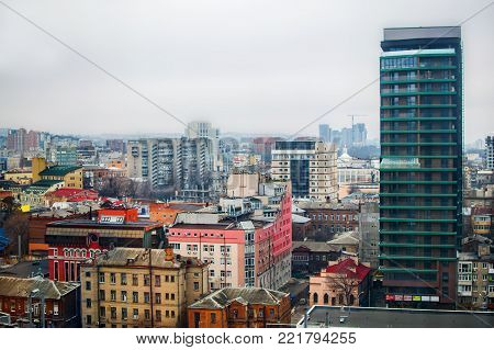 Rooftops of old and new modern city builddings. View of the winter Dnipro city in cloudy weather