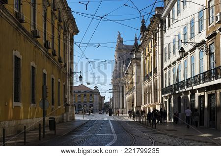 Lisbon, Portugal - October 22, 2017: Street scene in the downtown (baixa) of Lisbon with people in a street and the Comercio Square (Praca do Comercio) on the background, in Lisbon, Portugal