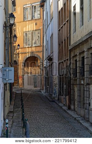LYON, FRANCE, January 13, 2018 : Small street of the city center near Saint-Paul district. The Historic Center of Lyon was designated a UNESCO World Heritage Site in 1998.