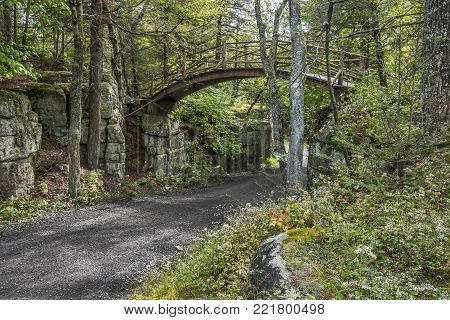 An old carriage road with a wooden footbridge crossing over in Minnewaska State Park Preserve.
