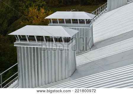 Metal corrugated roof with ventilation on apartment house house, closeup