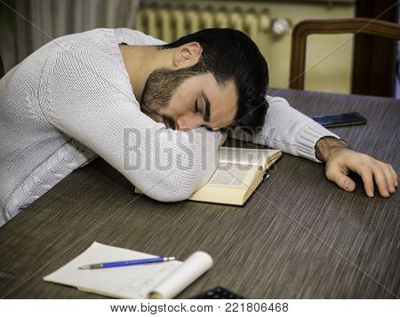 Over-worked, tired young man at home sleeping instead of working or studying, resting head over book. Tired male student falling asleep reading book
