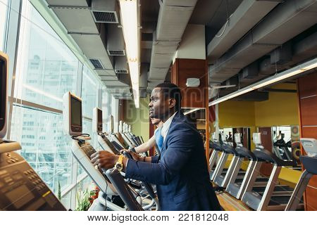 Portrait of young people with elliptic machine in the gym. African man is businessman in classic suit