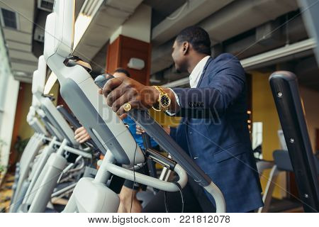 Active black man in classical suit exercising on elliptical trainer machine at indoor gym.