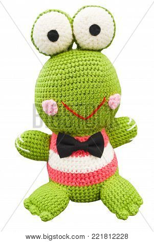 Crochet doll of lovely green frog smiling in Japanesse style with two big eyes on head, pink cheeks, put over shirt in pink and white with black bow tie, isolated white background and clipping path, hobby handmade work with yarn at home for woman