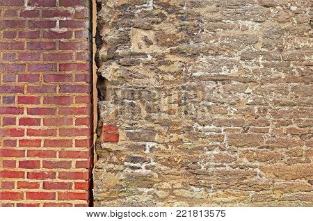 Split wall, part old rustic stone wall and part modern red brick wall with space for text. Old meets new.
