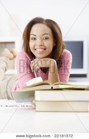 Porträt von glücklich Afro mature slut Studium zu Hause mit Büchern, in die Kamera Lächeln.?
