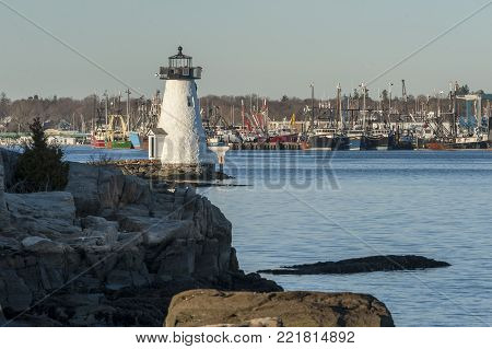 New Bedford, Massachusetts, USA - December 21, 2017:  Late afternoon view of Palmer's Island lighthouse on the Acushnet River with Fairhaven fishing fleet in background