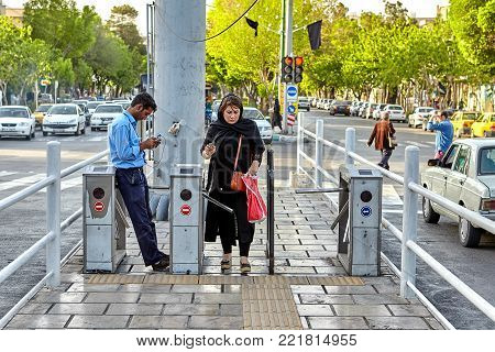 Isfahan, Iran - April 23, 2017: One adult Muslim woman passes to the bus station through an automatic ticket turnstile.