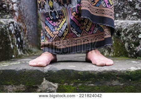 Close up view on man foot in balinese indonesian sarong. National clothes detail.