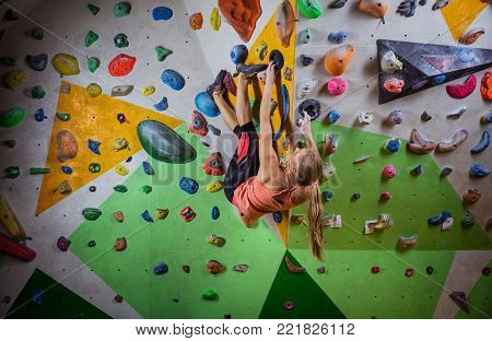 Young woman bouldering on overhanging wall in indoor climbing gym, making challenging move to reach final handhold