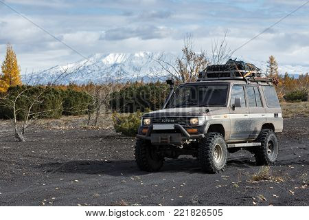 KAMCHATKA PENINSULA, RUSSIAN FAR EAST - OCTOBER 2, 2016: Japanese 4x4 automobile Toyota Land Cruiser Prado prepared for off-road tourism and long travel through mountains is parked on volcanic slag.