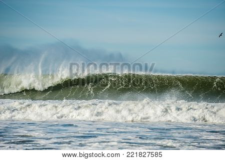 Offshore wind blows tops of large right hand wave with Channel Island in background,