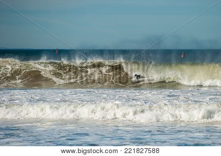 Black wetsuit of California surfer show as offshore winds create large and hollow tube waves on a close out set.