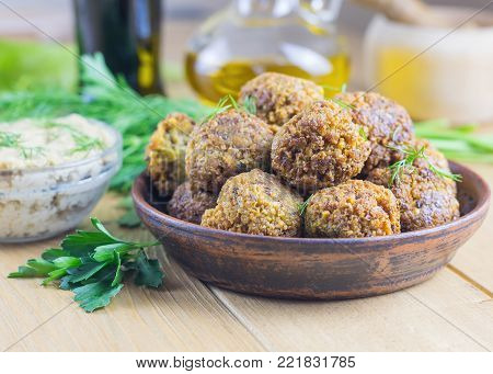 Freshly prepared falafel with tahina sauce, herbs and soy sauce on a wooden table. Eastern vegetarian meal of chickpea.