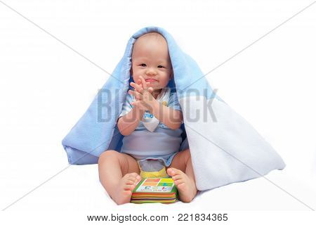 Happy little toddler baby boy smiling wearing bodysuit, bib and diaper sitting under blue blanket  clapping his hands isolated on white, 11 months old baby reading his first book, Happy kid concept