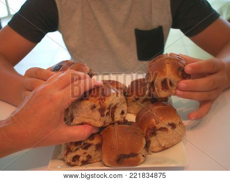Hands grabbing choc chip filled Hot Cross Buns, a delicious traditional Easter snack.